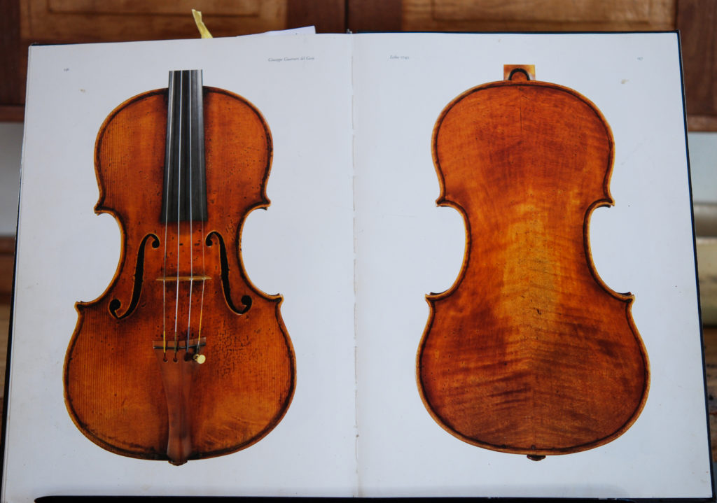 A book open to photographs of the Leduc Guarnieri violin