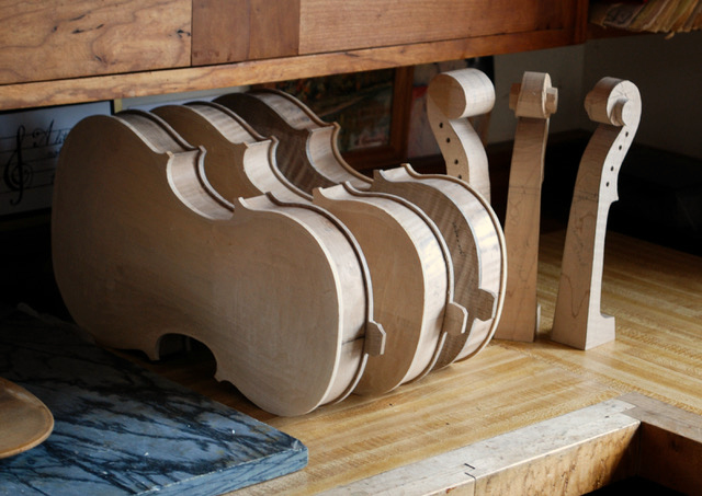 three unfinished violin bodies on a workbench next to three unfinished violin scrolls